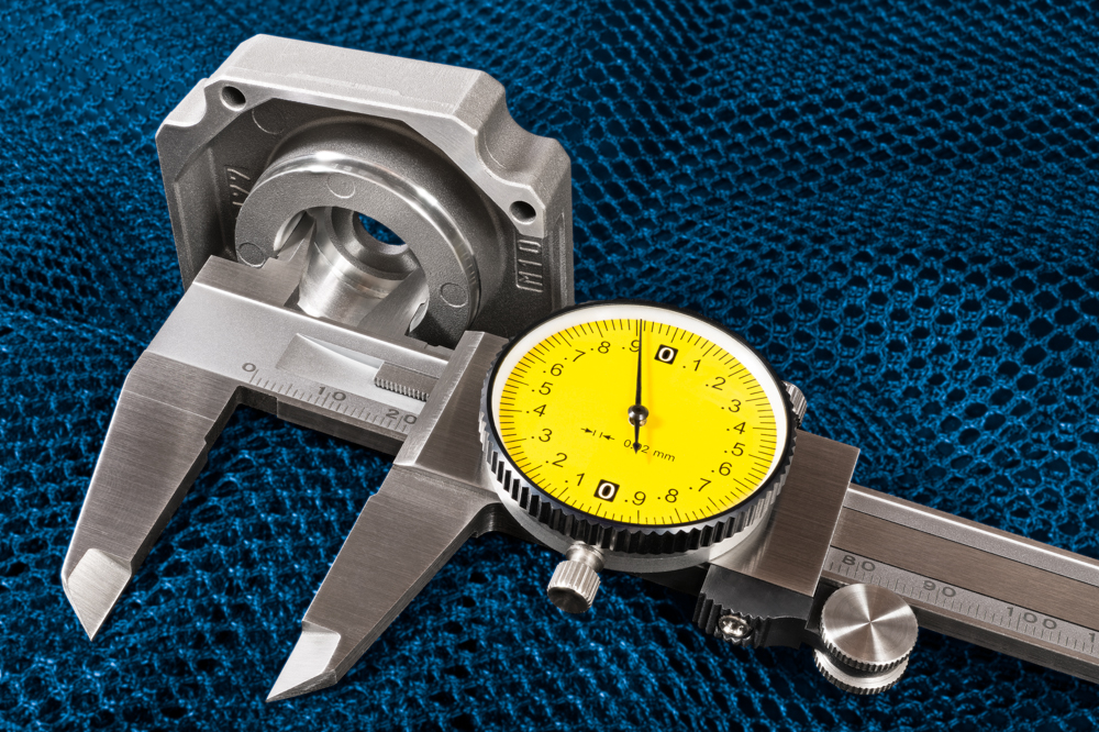 Measurement of aluminium cast of inner bearing housing. Precise metal tool. Round yellow dial. Copy space. Quality inspection