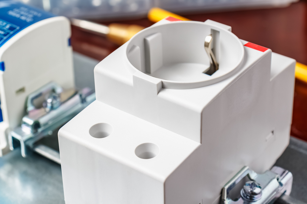 Electric socket in white plastic case installed on DIN rail of electrical panel close-up. Electrical panel assembling